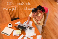 Hispanic couple at the kitchen table paying their bills online.  He is seated and she is leaning on him.  Bills and receipts are on the table along with a cup of coffee and the laptop